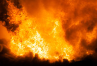 Arson or nature disaster - burning fire flame on wooden house ro